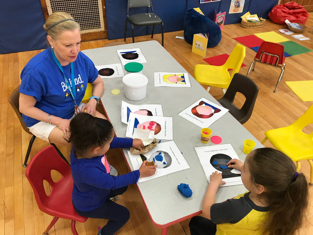 Photo of 2 young children sitting with a teacher making expressions on paper faces with play-doh