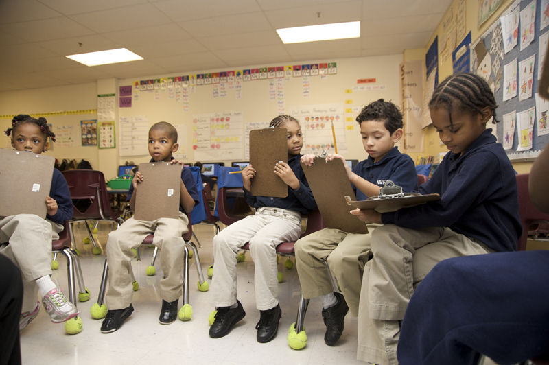 Children with clipboards sitting in a circle in a classroom