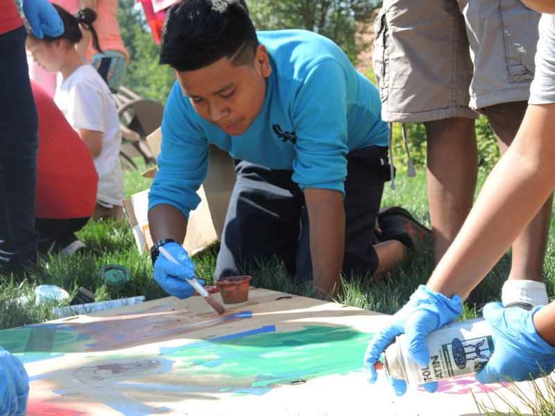 a boy painting outside