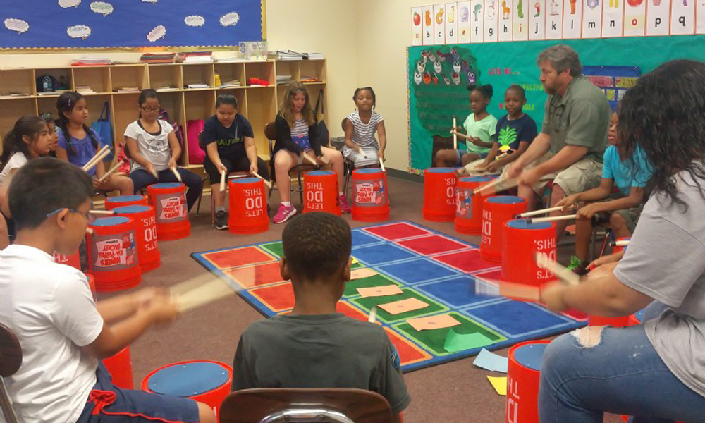 Large group of kids sitting at a drumming circle in a classroom