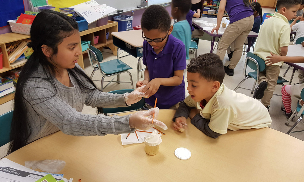 woman helping young boys conduct a science experiment