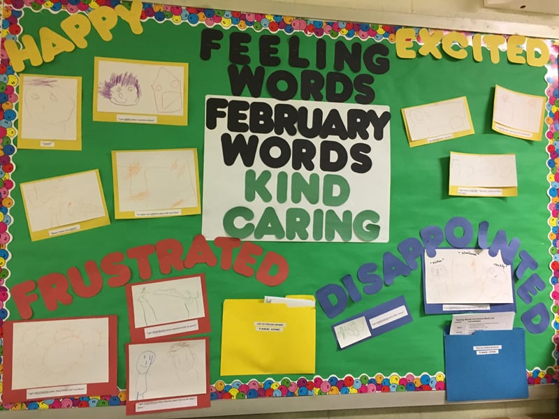 Bulletin board displaying young children's artwork and a caption that says February words: kind, caring