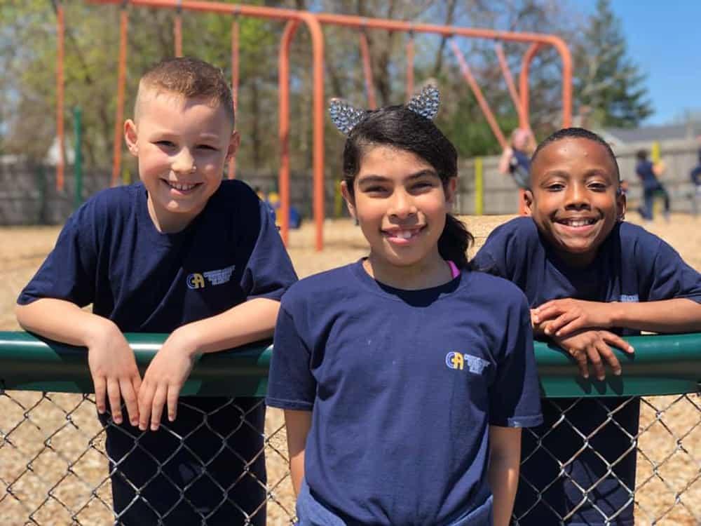 3 smiling children in a playground