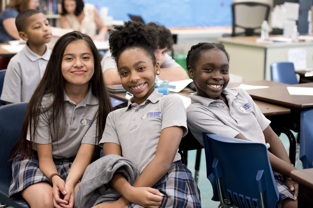 3 young girls smiling in a classroom